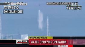 Zwei Helikopter werfen Wasser über Reaktor 3 ab.