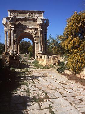 """Die Reste einer Prachtstraße und des römischen Ehrenbogens des Septimius Severus in der Ruinenstätte """"Leptis Magna"""" in Libyen."""