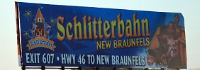 """Ein Werbeschild für die """"Schlitterbahn"""", die Hauptattraktion im Vergnügungspark, aufgenommen an einem Highway, der von New Braunfels nach Weimar, Texas, führt."""