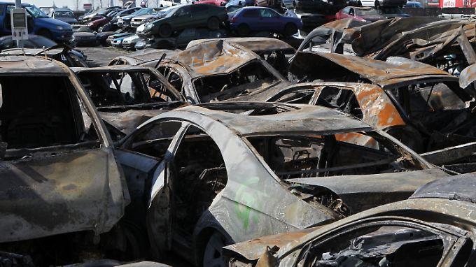 Auf dem Geländes eines Autoverwerters nahe Rostock stehen die ausgebrannten Wracks der Massenkarambolage auf der A19.