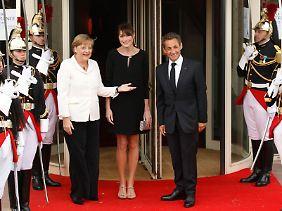Kanzlerin Merkel wird vom Ehepaar Sarkozy begrüßt.