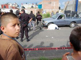 Kinder stehen vor einem abgesperrten Tatort im mexikanischen Morelia.