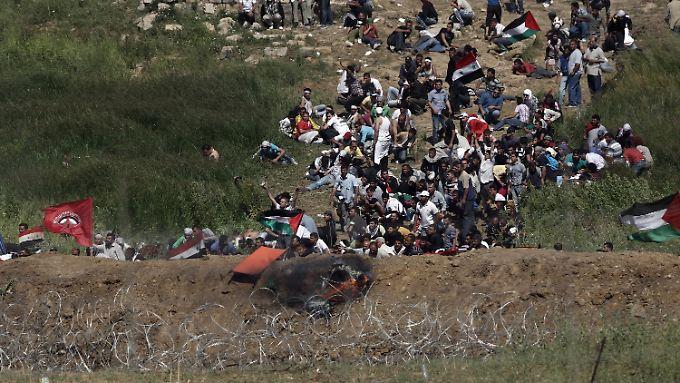 Palästinensische Demonstranten gehen in Deckung, nachdem israelische Soldaten auf den Golanhöhen das Feuer eröffnet haben.