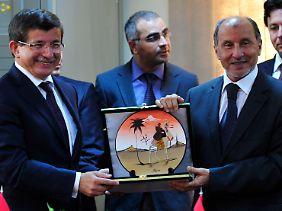 Der türkische Außenminister Ahmet Davutoglu (links) posiert in Bengasi neben dem Vorsitzenden des Nationalen Übergangsrats, Mustafa Abdel Dschalil. Die Türkei hat den Übergangsrat offiziell anerkannt.