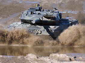 Ein Kampfpanzer vom Typ Leopard 2 in voller Fahrt auf dem Truppenübungsplatz Munster.