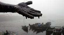 Die Hand beweist: Ölpest in China.
