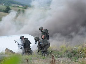 27. Juli: KFOR-Soldaten durchkämmen das Gelände nach maskierten serbischen Extremisten, nachdem der Grenzübergang Jarinje in Brand gesteckt worden war.