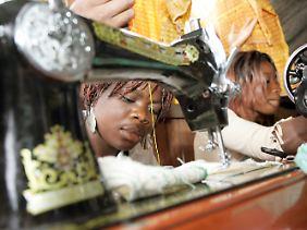 Hilfsprojekt im Kongo: Junge kongolesische Frauen arbeiten an Nähmaschinen in einem Elendsviertel Kinshasas.
