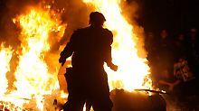 Unbekannte wärmten sich an einem großen Feuer.