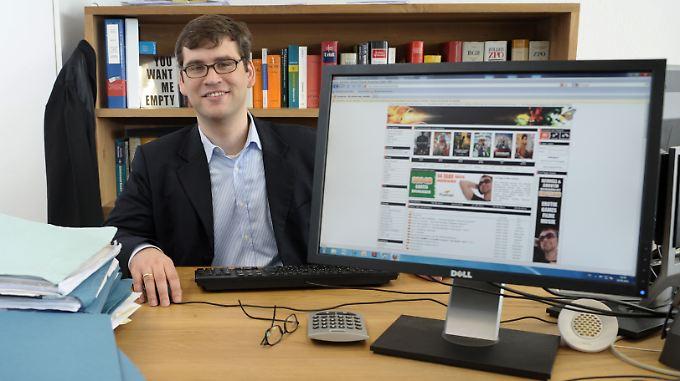 Der Hamburger Medienrechtsanwalt Alexander Wachs in Hamburg an seinem Schreibtisch hinter einem Computermonitor, auf dem die Website eines Download-Portals für Musik und Filme zu sehen ist.
