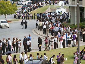 Arbeitssuchende stehen Schlange vor einer Job-Messe.