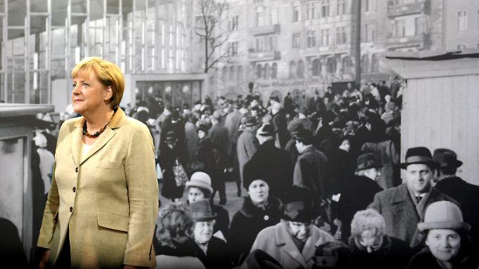 """Bundeskanzlerin Merkel  während der Eröffnung der Ausstellung """"GrenzErfahrungen. Alltag der deutschen Teilung"""" vor einem historischen Foto."""