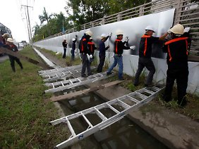 Arbeiter bereiten ihre Fabrik auf die Fluten vor.