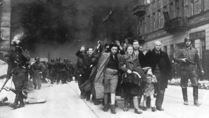 Deutsche Soldaten deportieren Juden aus dem Warschauer Ghetto in Vernichtungslager.