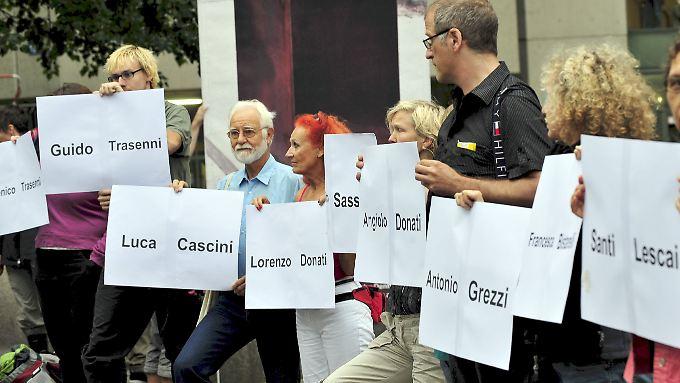 Demonstranten erinnern mit Namensschildern an die 14 Opfer des Massakers in Falzano di Cortona, während vor dem Schwurgericht I in München der Prozess gegen Josef Scheungraber läuft.