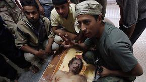 Gaddafis Leichnam wird in einem Kühlhaus aufgebahrt - seine Gegner posieren mit dem Ex-Diktator.