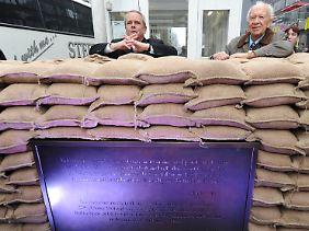 Charles C. Clay (l) und Sergej Chruschtschow hinter Sandsäcken am Checkpoint Charlie vor der Alliierten Kontrollbaracke bei der Enthüllung einer Gedenktafel.