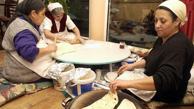 """Türkische Frauen in einem Restaurant in Kreuzberg fertigen auf tradtionelle Art """"Gözleme"""", ein anatolisches Teiggericht."""