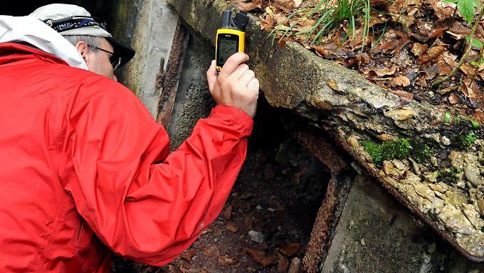 """Ein """"Geocacher"""" sucht vor dem Eingang eines Bunkers in einem Wald mit Hilfe eines Satellitennavigationsgerätes (GPS) ein verstecktes Behältnis, einen Cache ..."""
