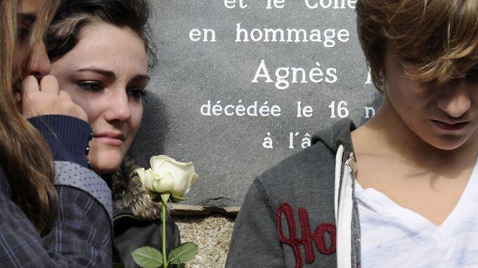 """Schüler des Internats """"Cevenol International"""" in Le Chambon-sur-Lignon stehen vor einer Tafel, die an ihre ermordete Mitschülerin Agnes erinnert."""