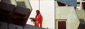 Ein bewaffneter Polizeibeamter im Trainingsanzug sichert am 5. September 1972 im Olympischen Dorf in München den Block, in dem Terroristen die israelischen Geiseln festhalten
