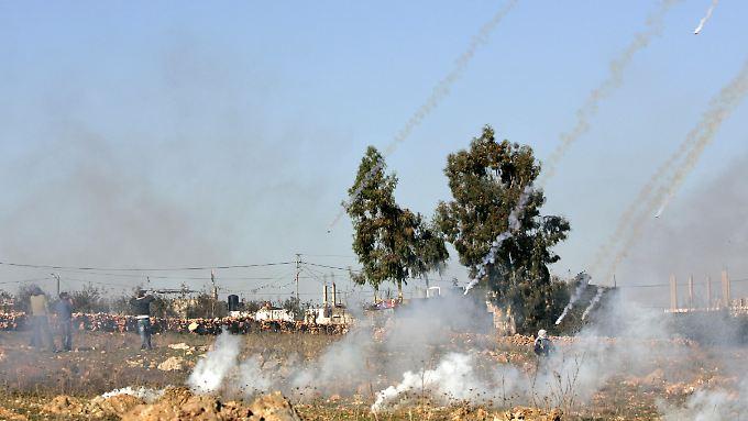 Israelische Soldaten beschießen palästinensische Demonstranten in der Westbank mit Tränengas.