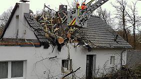 Arbeiter zersägen in Wuppertal einen Baum, der in das Dach eines Hauses gestürtzt ist.