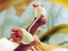 Auf der Frühgeborenenstation der Universität in Leipzig umsorgt eine Stationsschwester ein mehrere Wochen zu früh geborenes Mädchen, das in einem Inkubator liegt.