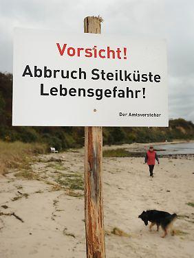 Warnschild, das auf die Abbruchgefahr an der Steilküste bei Lobbe hinweist.