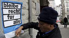 Ein illegaler Einwanderer befestigt an der Jakobskiche in Zürich ein Plakat.