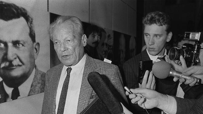 23. März 1987: Willy Brandt hat soeben seinen Rückzug vom Parteivorsitz verkündet. Nun wird er von Reportern bestürmt.