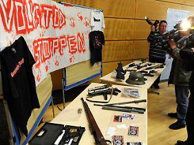 """Die Polizei präsentiert die gefundenen Waffen - und ein Transparent mit der Aufschrift """"Volkstod stoppen""""."""