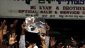 Muslime in Yangon zeigen Bilder getöteter Menschen.