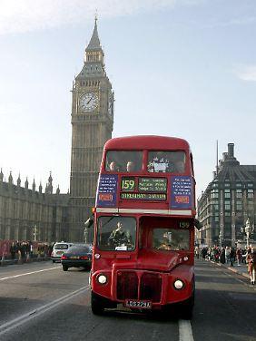 """Roter Doppeldeckerbus vor dem Turm mit der Glocke """"Big Ben""""."""