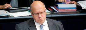 Mit geschlossenen Augen, das Handy griffbereit, nimmt Umweltminister Altmaier an der Sitzung des Bundestags teil.