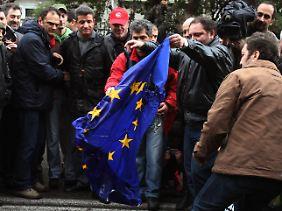 In Athen versuchen Griechen, eine EU-Flagge zu verbrennen.