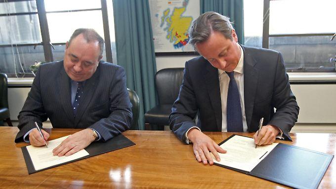 Alex Salmond und David Cameron setzen ihre Unterschrift unter das Dokument.