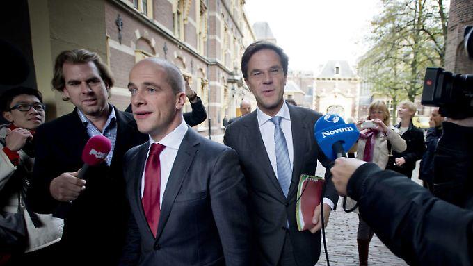 Mark Rutte (mit blauer Krawatte) und PvdA-Chef Diederik Samsom (rot) auf dem Weg ins Parlament.