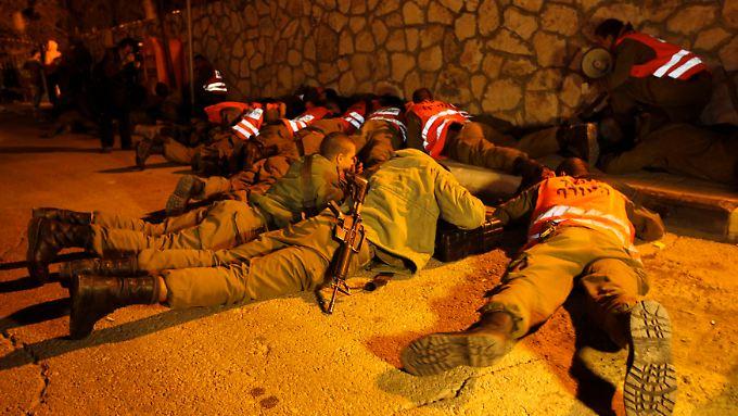 Israelische Soldaten schützen sich bei einem Raketenangriff auf die israelische Stadt Kirjat Mal'achi.