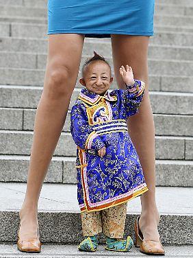He Pingping zwischen den Beinen der Russin Svetlana Pankratova, der Frau mit den angeblich längsten Beinen der Welt, bei einem Foto für das Guinness-Buch der Rekorde 2009.