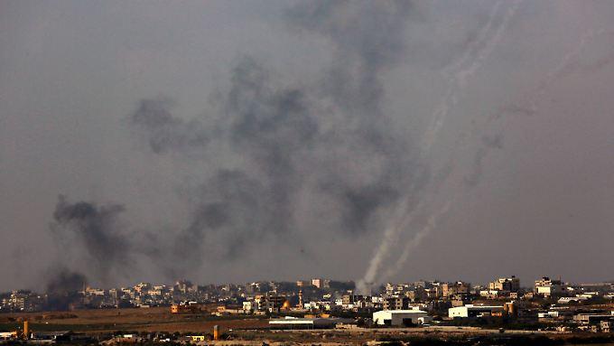 Einschläge israelischer Angriffe in Gaza-Stadt. Zugleich sind die Flugbahnen von Raketen zu sehen, die in Richtung Israel abgefeuert wurden.