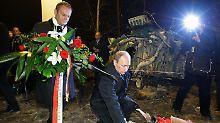 Der russische Ministerpräsident Wladimir Putin und sein polnischer Kollege Donald Tusk legen Blumen an der Unglücksstelle nieder.