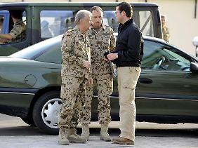 Guttenberg (r) spricht mit Generalinspekteur Wieker (l) und Brigadegeneral Leidenberger in Temes.