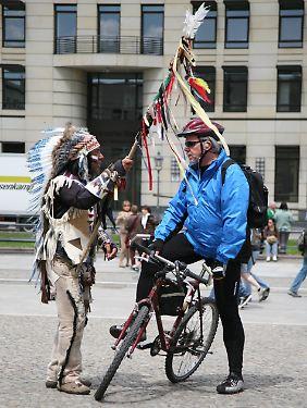 """Ein Berlin-Tourist zu Rade bekommt auf dem Pariser Platz gute Wünsche mit auf den Weg von einem """"Indianer""""."""