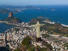 Christus breitet seine Arme über Rio aus: Eine Zahnradbahnfahrt zum Corcovado, auf der die Figur trohnt, oder eine Seilbahnfahrt auf den gegenüberliegenden Zuckerhut gehört für viele Besucher zum Rio-Programm.