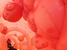 Besucher betrachten Wucherungen und Polypen in der 30 Meter langen Nachbildung eines menschlichen Darmes.