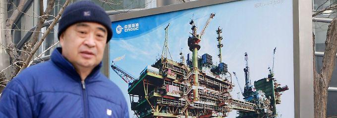 Zufällig ins Bild gelaufen: In Peking wirbt der staatliche Ölkonzern China National Offshore Oil Corp (CNOOC) vor seiner Zentrale mit großformatigen Bildern für die verstärkte Ölförderung.