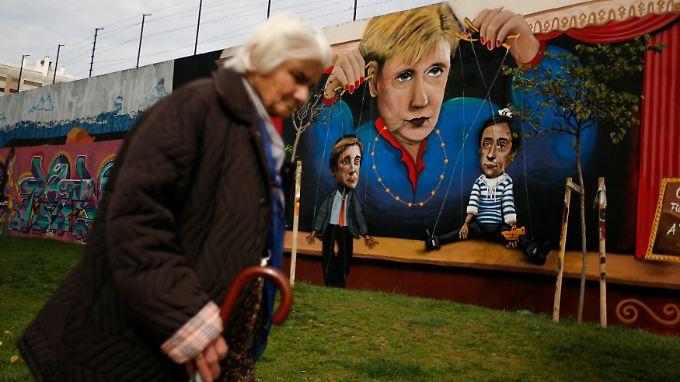 Eine alte Frau läuft in der portugiesischen Hauptstadt Lissabon an einem Graffiti mit Kanzlerin Merkel vorbei. Das Misstrauen der Europäer beschränkt sich nicht auf Politiker. Sie misstrauen sich auch gegenseitig.