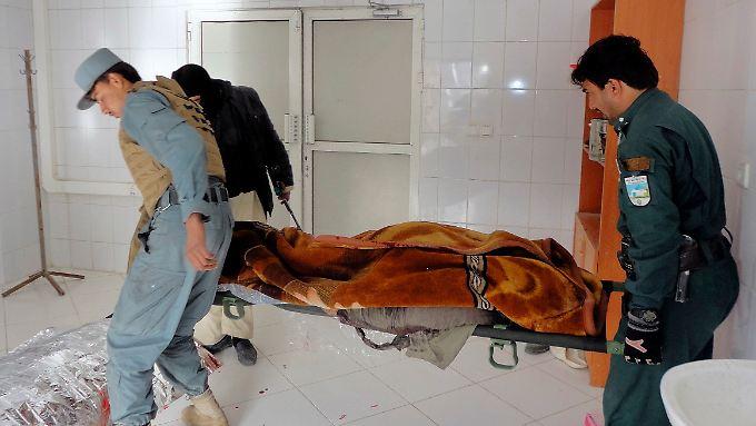 Afghanische Polizisten mit einem der Opfer im Krankenhaus von Chost.