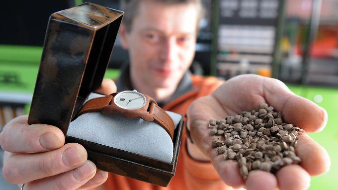 """Christian Anselment, Ingenieur beim Institut für Chemische Technologie (ICT) in Pfinztal zeigt ein Uhrengehäuse und die Verpackung, die aus dem Bio-Kunststoff """"Arboform"""" hergestellt sind. Rechts ist das Granulat des Kunstoffes zu sehen."""
